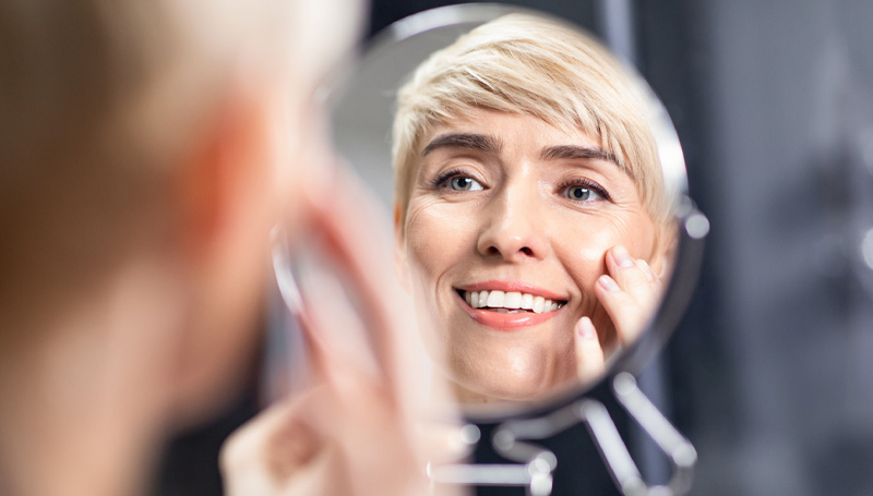 woman in her 50s checking her eyes in a mirro