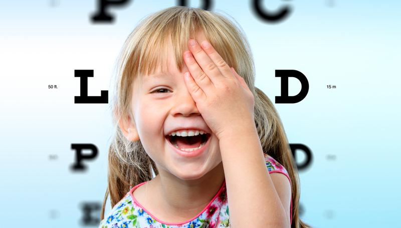 child posing for an eye exam