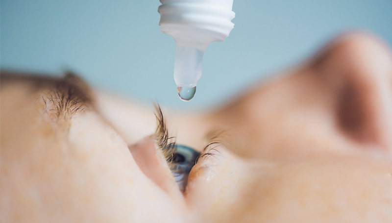 closeup of eye drops going into an eye