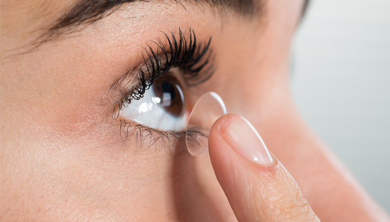 closeup of woman inserting contact lens into her eye