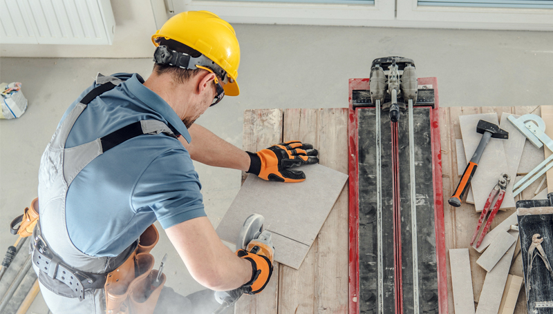 construction worker cutting through material while wearing safety glasses