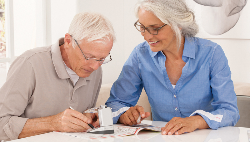 couple with low vision using magnifying device