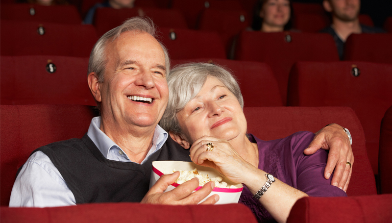 elderly couple watching a movie in the theater