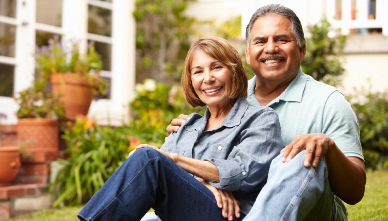 senior couple posing in front yard