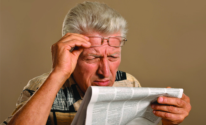 older man squints to read the newspaper