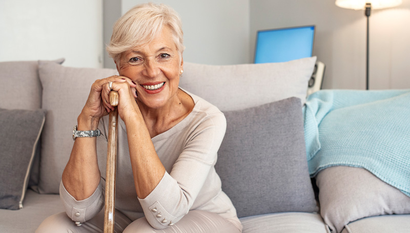 elderly woman smiling while sitting on couch