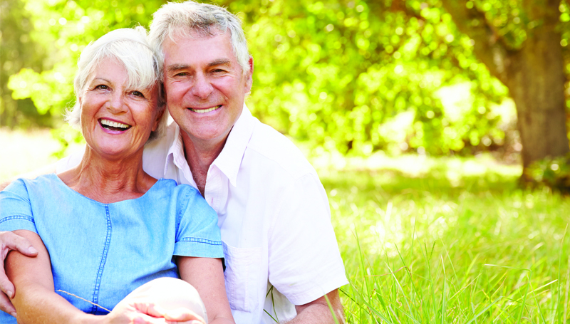 happy retired couple sitting under a tree