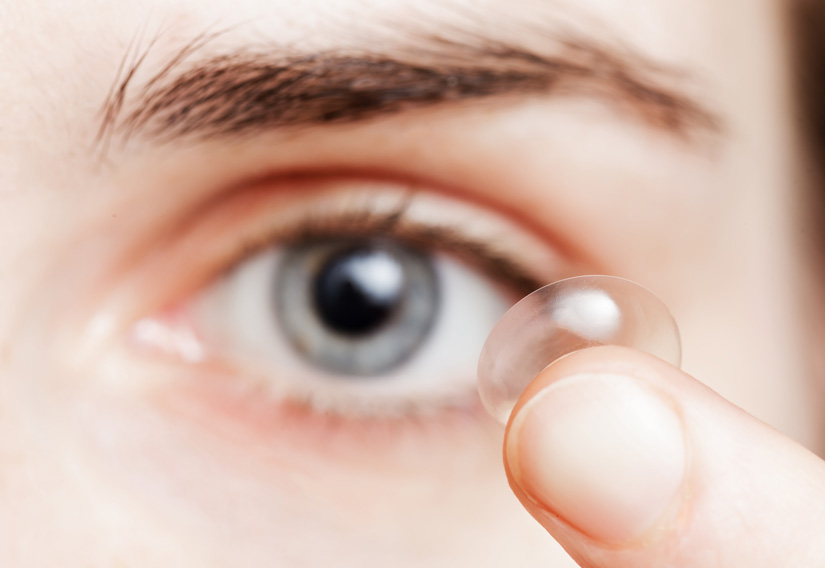 woman with contact lens on her fingertip