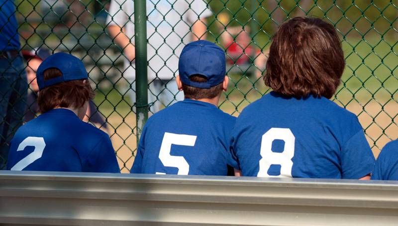 little league baseball players sitting on the bench at a game