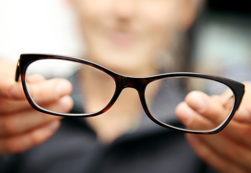 woman extending a pair of eyeglasses towards the camera