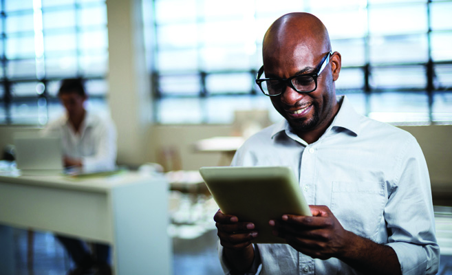 man in glasses looks down at tablet computer