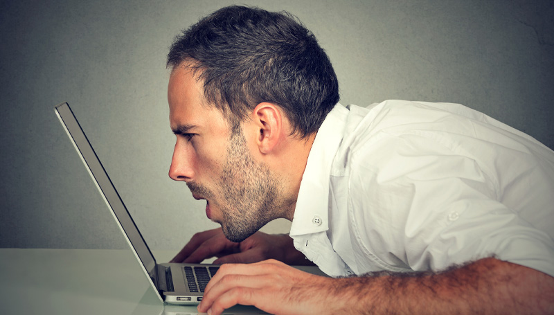 man straining to read laptop screen