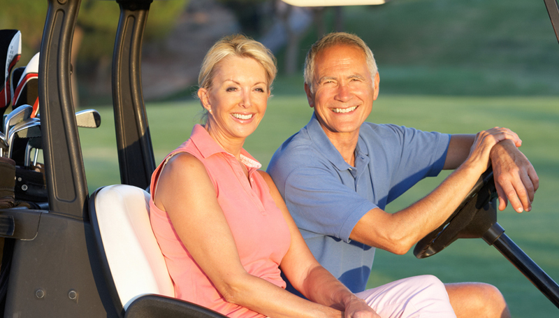 retired couple smiling in a golf cart
