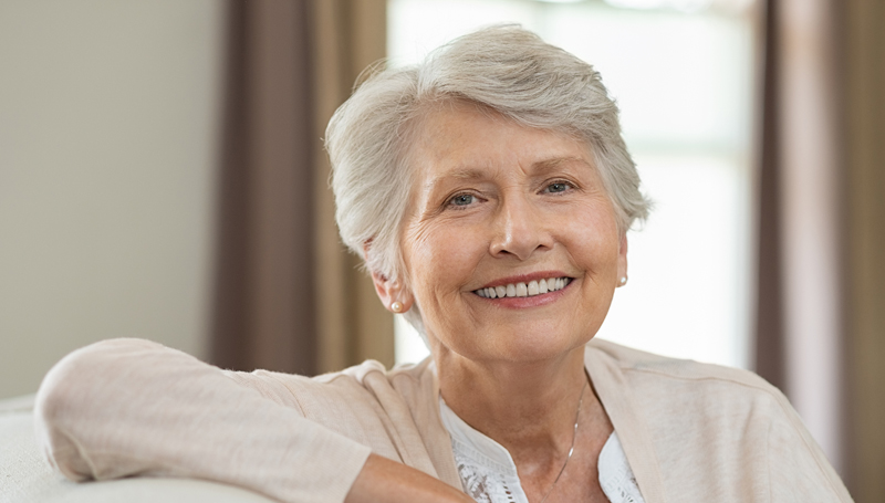 retired woman sitting on couch smiling