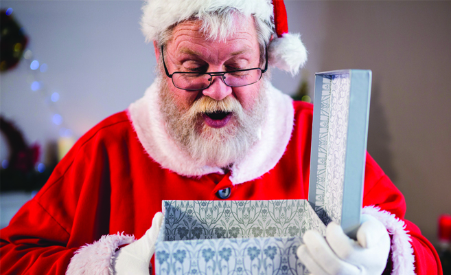 eyeglasses wearing santa opens a present