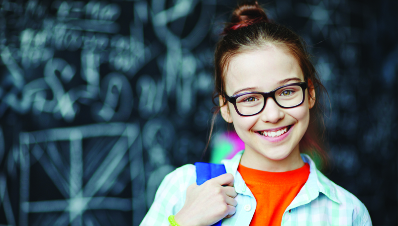school-aged girl in glasses in front of a chalkboard