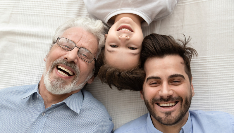 three generations of men smiling
