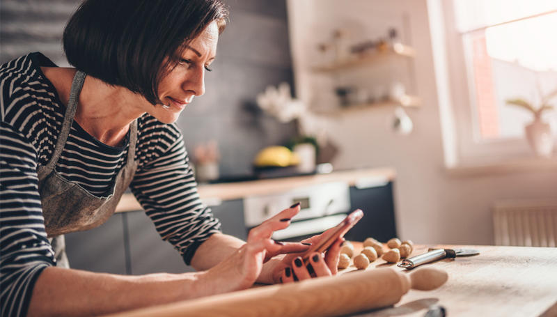 woman looking at her phone in the kitchen