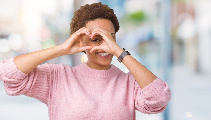 woman making a heart shape over her eye with her hands