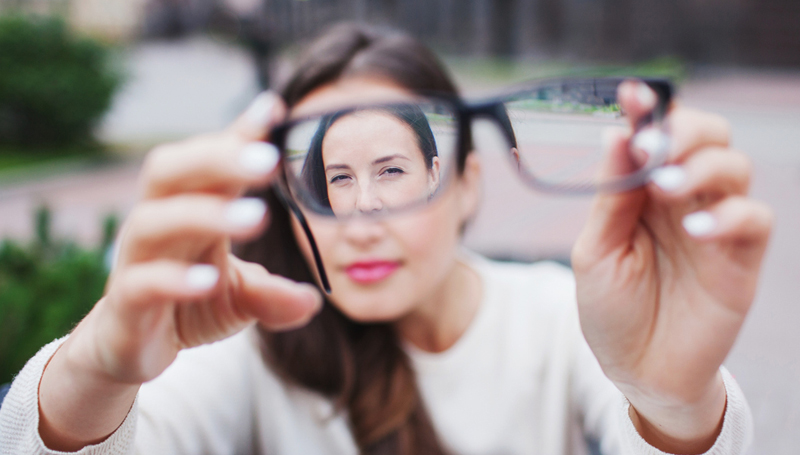 woman seen through glasses she's putting on someone else