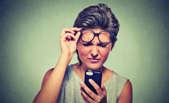 woman in glasses squinting to see phone screen