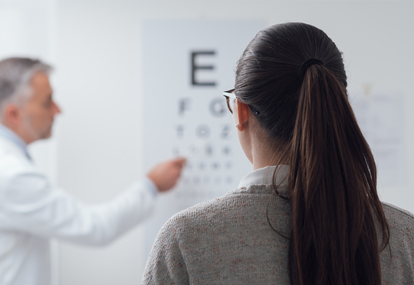 woman taking vision test by reading exam poster