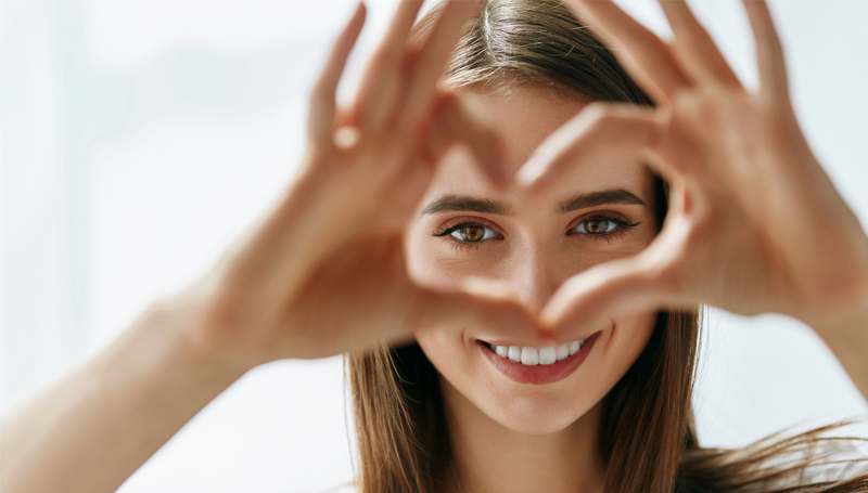 young woman making a heart shape with her hands